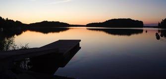 跳船在寂静的水中反射了在日落,在跳船的湿脚印 免版税库存照片