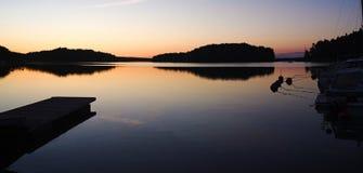 跳船在寂静的水中反射了在日落,在水的反射 免版税库存图片