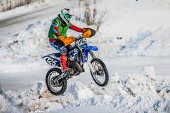 跳跃一辆摩托车的竟赛者在多雪的小山 库存照片