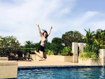 跳跃下来到游泳池的亚裔女孩画象 库存照片