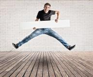 跳跃与一副白色横幅的年轻人 免版税图库摄影