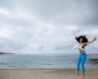 跳跃与一把白色伞的美丽的妇女在海滩 库存图片