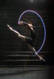 跳跃与一条五颜六色的体操丝带的优美的跳芭蕾舞者 图库摄影