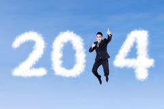 跳跃与云彩的愉快的商人2014年 免版税库存图片