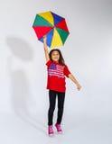 跳跃与五颜六色的umb的逗人喜爱的矮小的微笑的美国黑人的女孩 免版税图库摄影