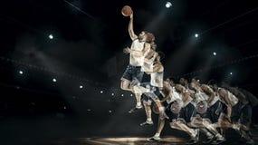 跳跃与在专业法院竞技场的球的蓝球运动员 拼贴画 免版税库存照片
