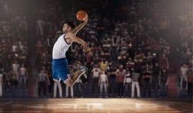 跳跃与在体育场的球的蓝球运动员 库存照片