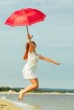 跳跃与在海滩的伞的红发女孩 免版税图库摄影