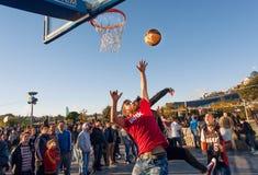 跳跃与在篮球操场的球的年轻人在普遍的城市节日期间 免版税库存照片