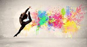 跳跃与在都市backg的五颜六色的墨水泼溅物的愉快的少年 免版税库存照片