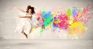 跳跃与在都市backg的五颜六色的墨水泼溅物的愉快的少年 库存照片