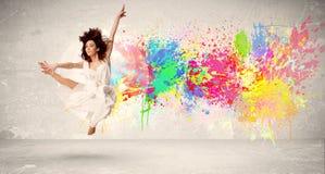 跳跃与在都市backg的五颜六色的墨水泼溅物的愉快的少年 图库摄影