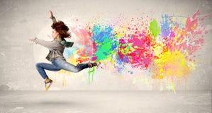 跳跃与在都市backg的五颜六色的墨水泼溅物的愉快的少年 库存图片