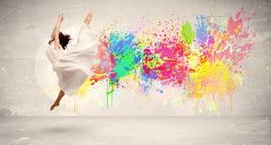 跳跃与在都市backg的五颜六色的墨水泼溅物的愉快的少年 免版税库存图片