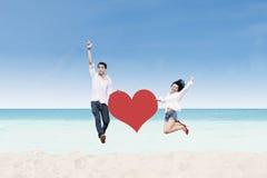 跳跃与心脏卡片的亚洲夫妇在海滩 库存图片