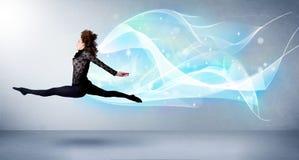跳跃与抽象蓝色围巾的逗人喜爱的少年在她附近 免版税库存照片
