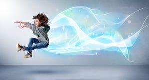 跳跃与抽象蓝色围巾的逗人喜爱的少年在她附近 免版税库存图片