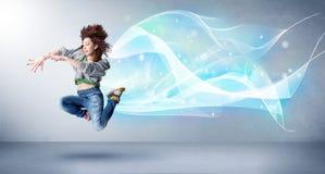 跳跃与抽象蓝色围巾的逗人喜爱的少年在她附近 库存照片
