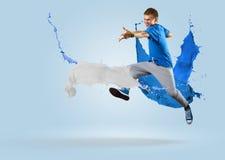 跳跃与油漆飞溅的年轻男性舞蹈家  图库摄影