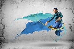 跳跃与油漆飞溅的年轻男性舞蹈家  免版税图库摄影