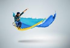 跳跃与油漆飞溅的年轻男性舞蹈家  免版税库存照片