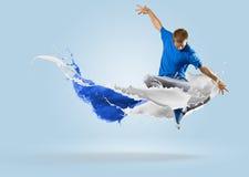 跳跃与油漆飞溅的年轻男性舞蹈家  库存图片