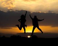 跳跃与美好的日落的两个女孩剪影  免版税库存照片