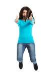 跳跃与赞许的年轻愉快的妇女 免版税库存图片