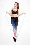 跳跃与跨越横线的一名微笑的健身妇女的画象 免版税库存图片