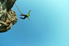 跳跃与绳索的峭壁 激动的小女孩 库存图片