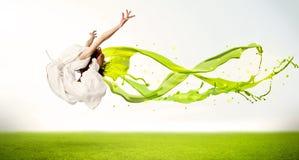 跳跃与绿色抽象液体礼服的俏丽的女孩 免版税库存图片