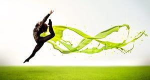 跳跃与绿色抽象液体礼服的俏丽的女孩 免版税库存照片