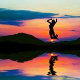 跳跃在日落的愉快的妇女剪影 免版税库存照片