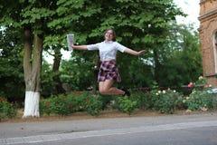 跳跃为喜悦的学校女孩 免版税库存图片