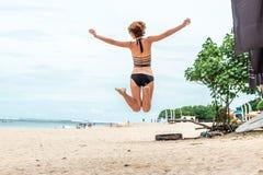 跳跃为在海滩的喜悦的美丽的年轻性感的妇女热带巴厘岛,印度尼西亚 晴朗的夏日场面 库存图片