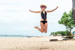 跳跃为在海滩的喜悦的美丽的年轻性感的妇女热带巴厘岛,印度尼西亚 晴朗的夏日场面 免版税库存照片