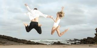 跳跃为在海滩的喜悦的年轻愉快的夫妇 库存照片