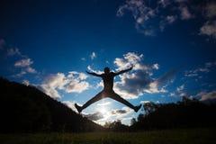 跳跃为在草小山的喜悦的一个人的剪影在天际线上 免版税图库摄影