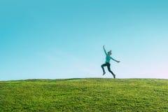 跳跃为在草小山的喜悦的单独亚裔妇女在天际线一在一个绿色领域的愉快的亭亭玉立的女孩飞行上反对蓝色夏天 库存照片