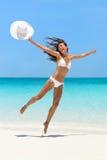 跳跃乐趣海滩假期的愉快的无忧无虑的女孩 免版税库存照片
