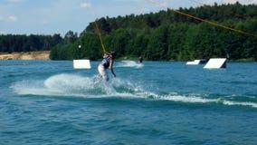 跳跃他的Wakeboard的一个人舷梯在缆绳公园,慢动作 滑水竞赛 股票视频