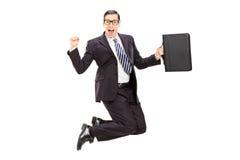 跳跃充满喜悦的激动的商人 免版税库存照片
