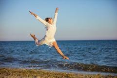 跳跃充满在海滩的喜悦的少妇 免版税图库摄影