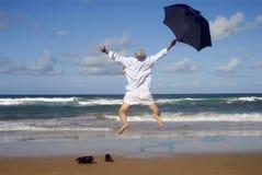 跳跃充满在海滩的幸福,退休自由概念的愉快的商人 库存照片