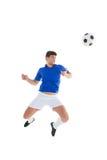 跳跃到球的蓝色球衣的足球运动员 库存图片