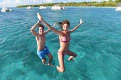 跳跃到从小船的海的快乐的青年人 库存图片