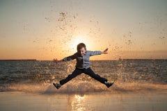跳跃反对巨大的波浪背景的滑稽的小男孩在美好的海日落 免版税库存照片