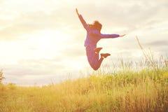 跳跃反对日落的少妇本质上 库存照片