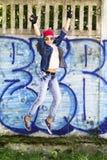 跳跃反对石墙背景的棒球帽和牛仔裤衬衣的逗人喜爱的年轻白肤金发的少年女孩 Hip Hop, 库存照片