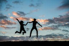 跳跃反对美好的日落的愉快的年轻夫妇 自由, en 免版税库存照片